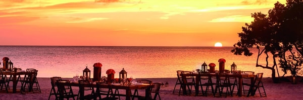 Tables on beach set for a reception with sun setting over the water in the background