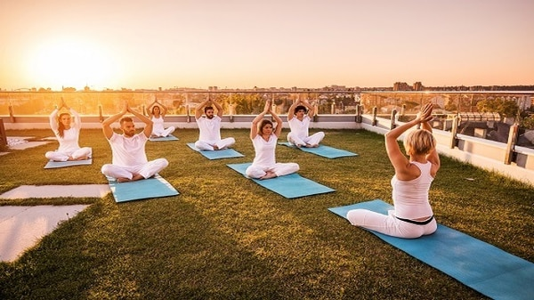 Group of people on the rooftop garden practicing yoga at sunset.