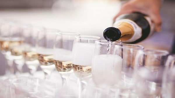 Line of glasses being filled with champagne