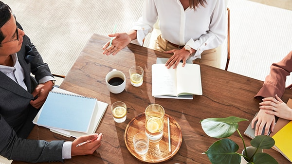 Cropped overhead of three people working at a wooden table in a Marriott meeting space