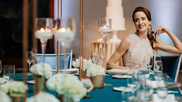 A smiling bride sitting at a banquet table