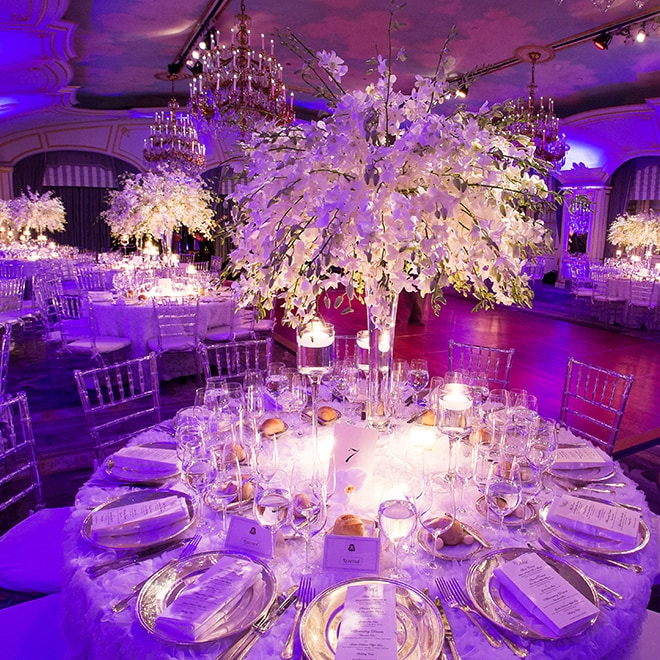 Round, formally set tables with tall floral arrangements