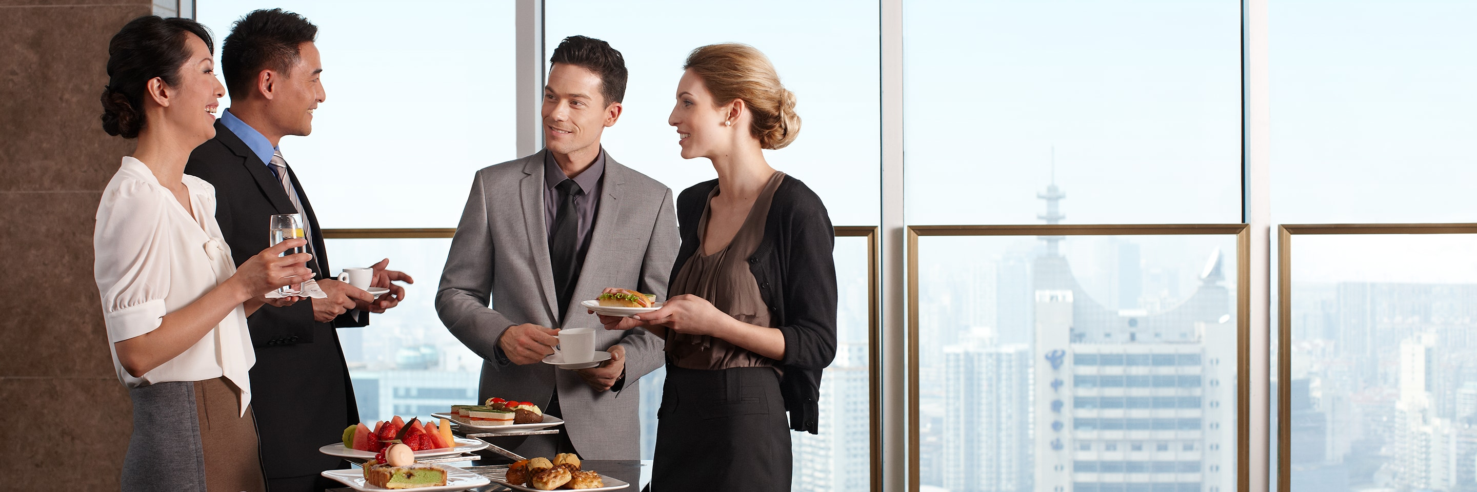 Four businessmen and women talk by a food display