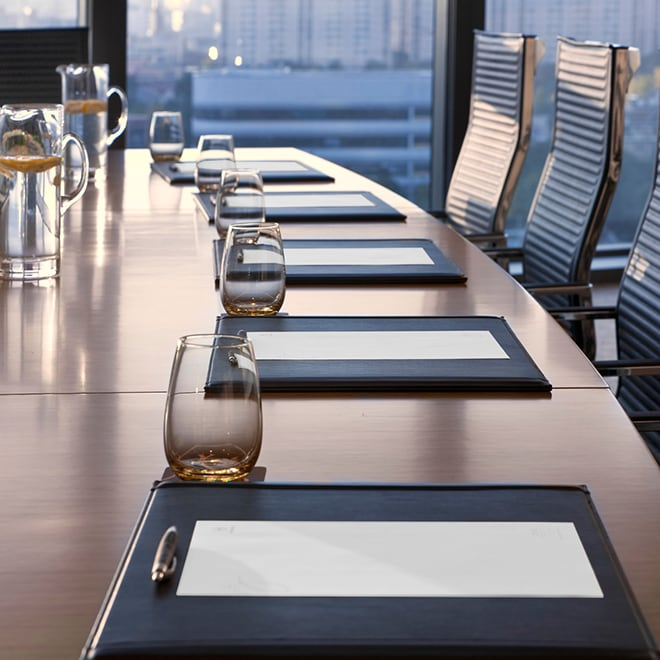 Conference table with notepads at each seat