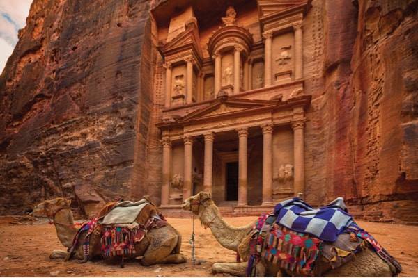 Camels resting in front of ancient building