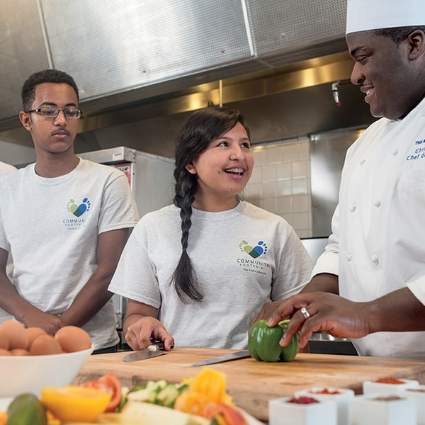 A male and female student talking to a chef