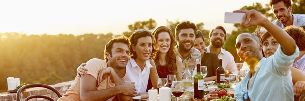 Six young men and women sit at a outdoor dining table with food and wine