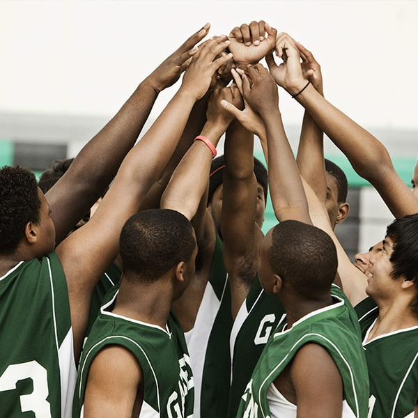 Male basketball players in a group high-five