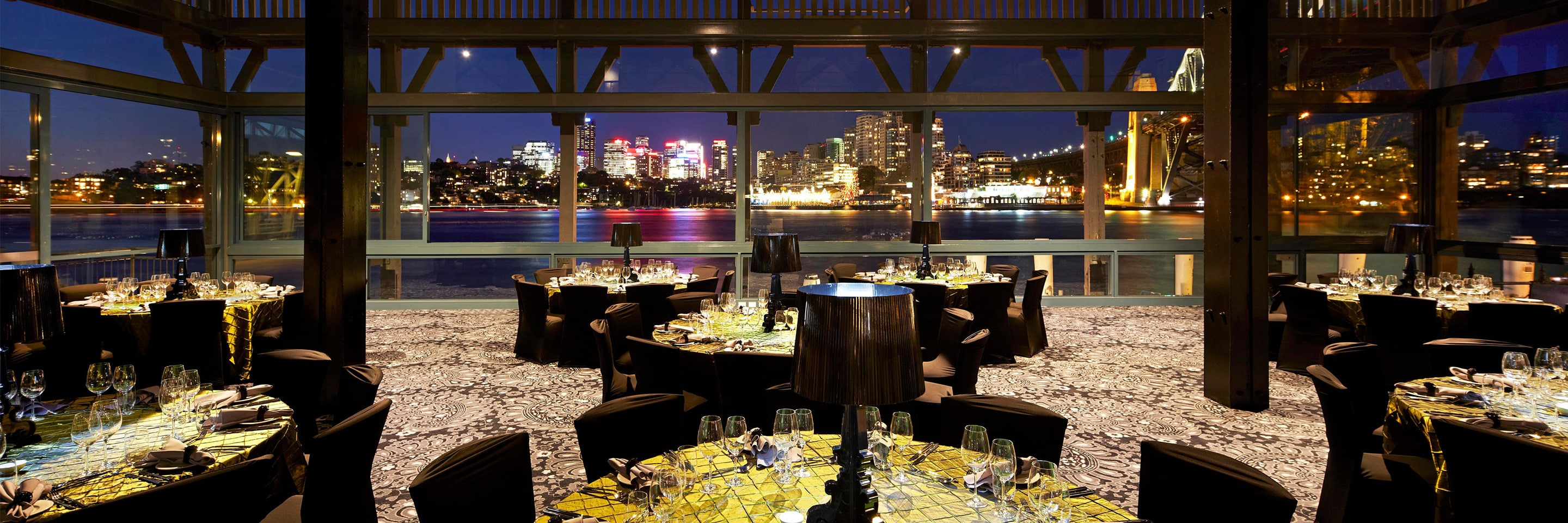 Outdoor dining at night overlooking river and cityscape
