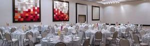 Ballroom wedding setup with round tables for eight