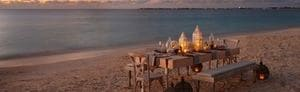 Beachfront themed dining setup with distinctive accents, candle lights, and ocean view at dusk