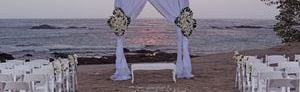 Beachfront wedding setup with wedding arch, rows of white chairs, and ocean view at sunset