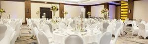 Large ballroom with classic wedding reception setup with round tables and floral centerpieces