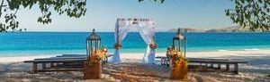 Beach wedding setup with wedding Arbor, benches, lanterns and ocean view on a sunny day