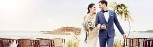Bride and groom in a beachfront wedding setup with chairs, floral arrangements and ocean view