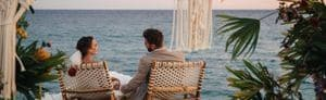 Bride and groom on a beach sitting on deck chairs with views of the ocean