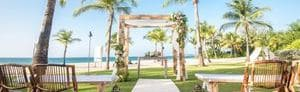 Wedding setup with wedding arch on manicured lawn, overlooking beach and ocean in the background