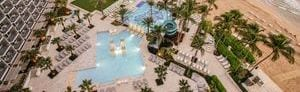 Aerial view of resort grounds peppered with palm trees, two outdoor resort pools, and adjacent beach