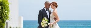 Bride and groom embracing on balcony with sparkling ocean view in the background