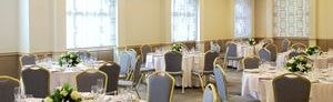 Brightly lit event space with round banquet tables for eight, each with white floral centerpieces.