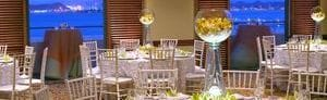 Event space with wedding setup, crystal centerpieces, and views of the harbor at dusk