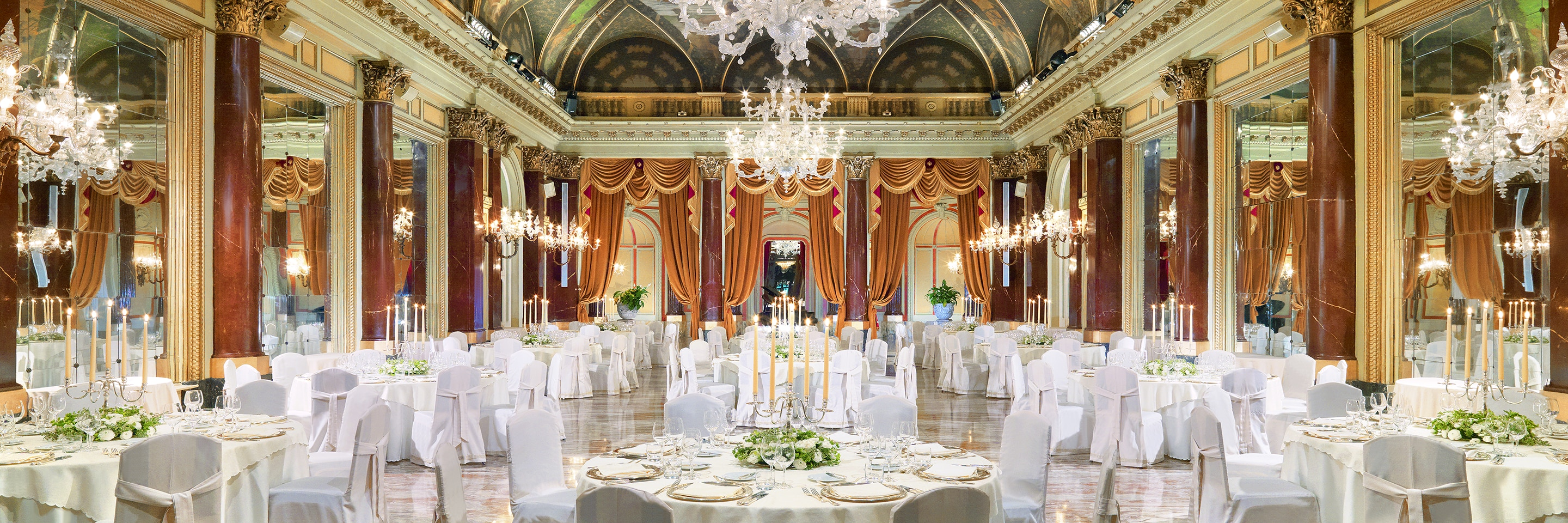 Opulent ballroom with lavishly set round dining tables