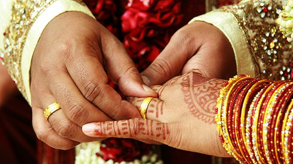 A male hand places a ring on a female hand decorated with henna