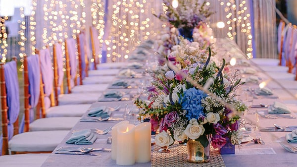 Tiny lights surround a long banquet table decorated for a wedding