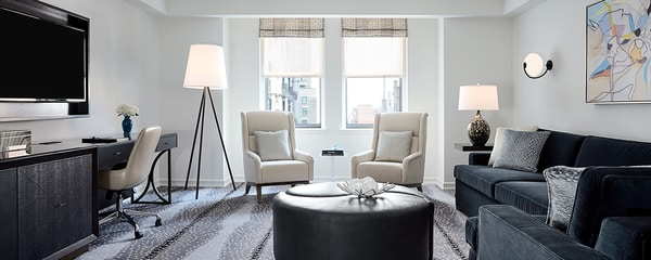 Hotel suite sitting area with chairs, sofa, work desk and wall-mounted TV