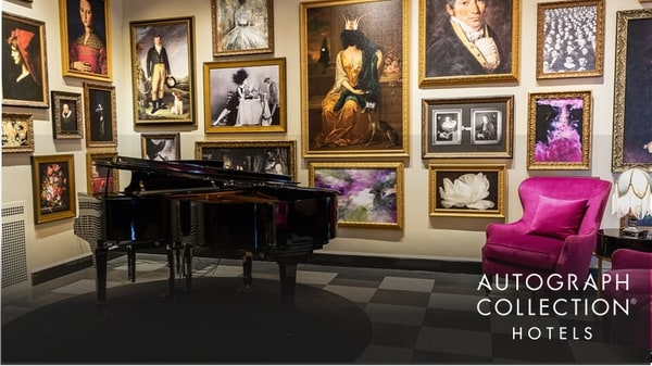 The Raleigh Room with piano, bright purple armchairs, and historic-themed portraits on the walls