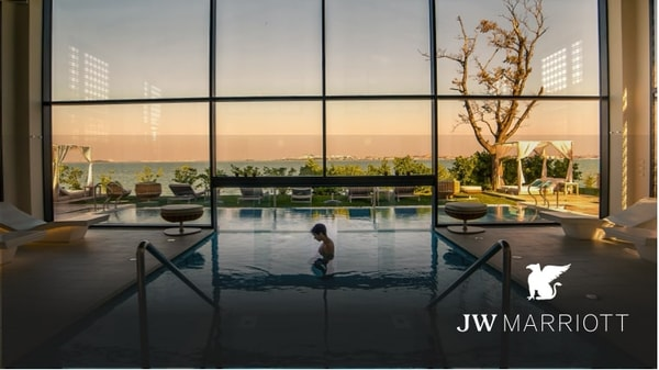 Spa style indoor/outdoor pool with towering window and a man standing in the water