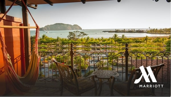 Balcony with table, chairs & a hammock overlooking the resort grounds and ocean beyond