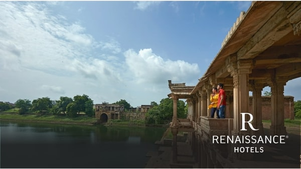 Couple sightseeing at a lake's shore lined with stone architectural walkway and columns