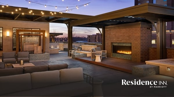Outdoor lounge at dusk with large fireplace, sofa seating and string lighting