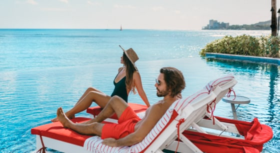 Couple sitting on red lounge chairs overlooking infinity pool and sparkling blue ocean