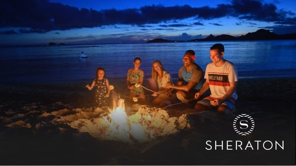 Five people roasting marshmallows around a fire on the beach with a boat in the water beyond