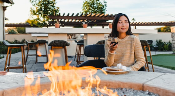 Woman sitting by firepit holding glass of wine with plate containing s'mores ingredients