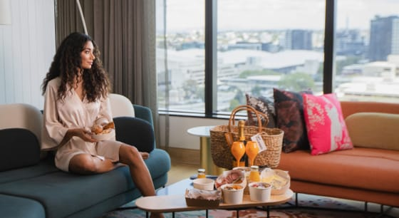Woman on sofa looking out window at city view next to coffee table filled with snacks