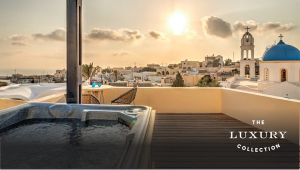 Aegean Suite balcony with Jacuzzi and stunning view over picturesque Santorini at dusk