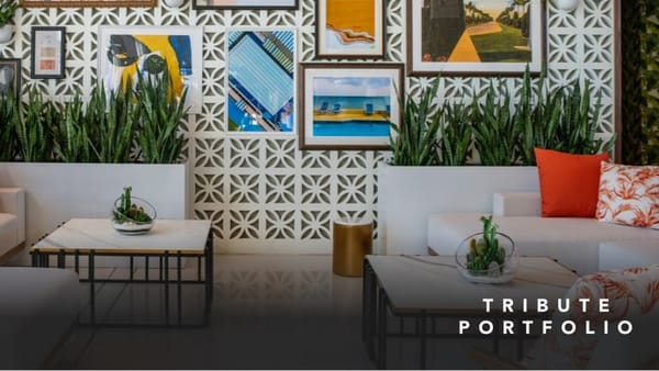 White modern sofas with orange throw pillows in front of a display wall of framed artwork