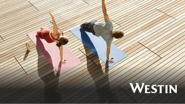 View from above of a man and woman doing side planks on yoga mats
