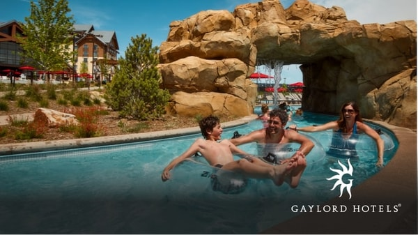 A family having fun in a water park pool with a rocky arch and a resort in the background in the lazy river at Arapahoe Springs.