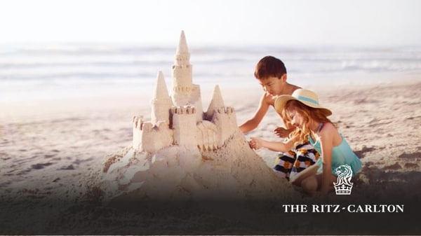 Two children on the beach building a large sand castle