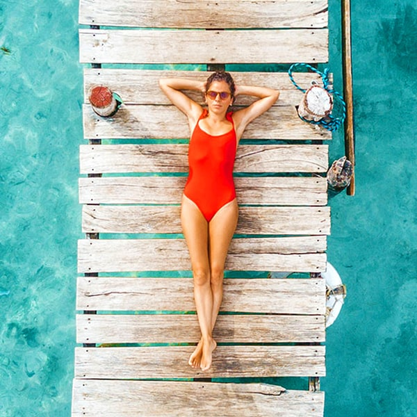 Woman on a float in the pool on a sunny day.