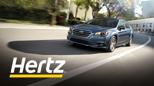 Subaru driving down road with Hertz logo.