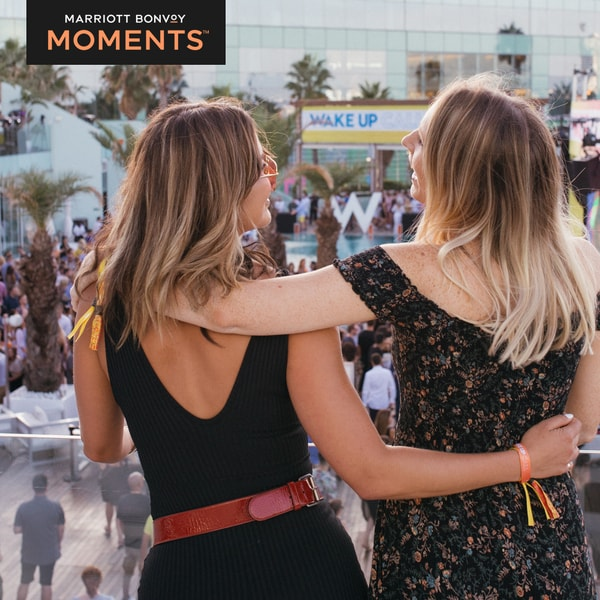 Two friends enjoying Wake Up Call festival and Marriott Bonvoy Moments logo