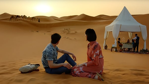 Couple sitting in the desert looking at the sunset.