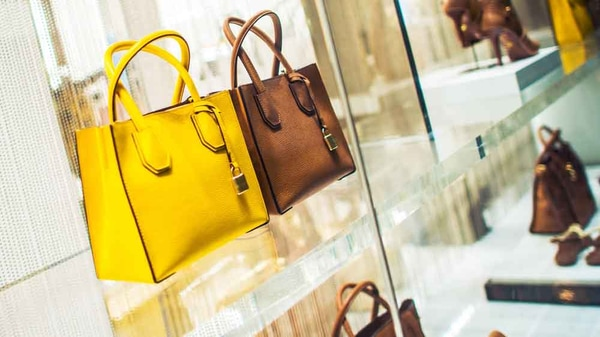 A yellow purse and a brown purse on a shelf