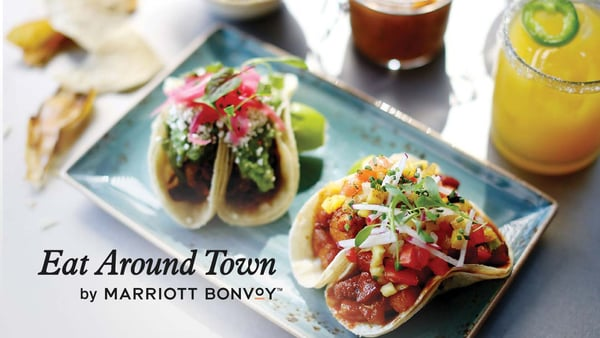 Restaurant tacos on a plate with Eat Around Town by Marriott Bonvoy logo