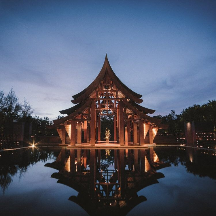 A dramatically lit pagoda at night, reflected in a pool of water